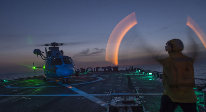 Boatswain's Mate 2nd Class Marcus Jones, from Anderson, S.C., directs a helicopter during flight operations aboard the guided-missile destroyer USS Laboon (DDG 58). | Military Times >>