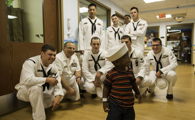 Sailors assigned to the Arleigh Burke-class guided-missile destroyer USS Cole play with a patient during a visit to Broward Health Medical Center during Fleet Week Port Everglades 2015.  | Military Affairs >>