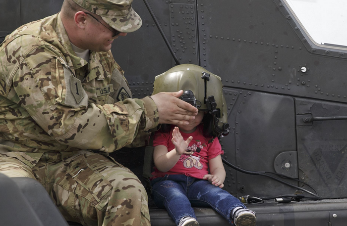 A soldier holds a pilot helmet for a child posing on an Apache attack helicopter in Ploiesti, Romania. | Military Times >>