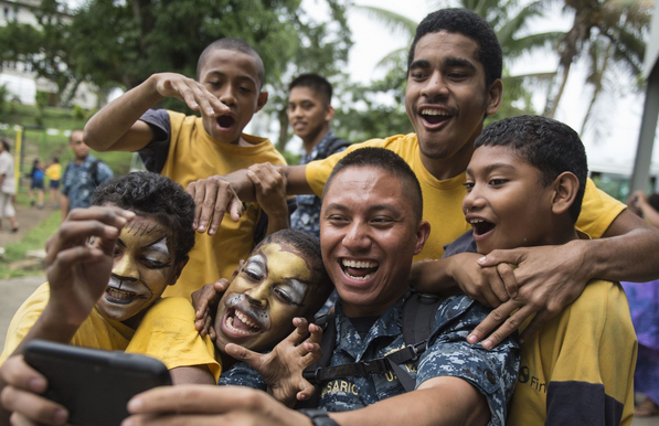 Lt. j.g. Jomer Belisario, a disbursing officer from Sacramento, Calif., takes a selfie with Fijian students at Hilton Special School during Pacific Partnership 2015 in Suva, Fiji. | Military Times >>