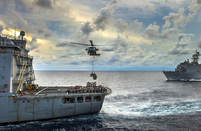 An MH-60S Seahawk helicopter lifts pallets of supplies from the flight deck of the Military Sealift Command fleet replenishment oiler USNS Walter S. Diehl during a vertical replenishment with the amphibious assault ship USS Essex in the South China Sea. | Military Times >>