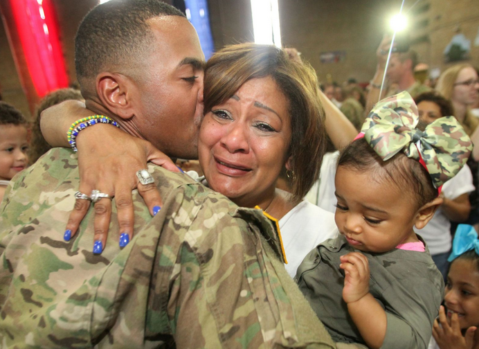 Sgt. Jesse De La Cruz, 29, of Passaic, NJ kisses his mother, Mari Gumann of Vernon as she holds his daughter, Khloe De La Cruz, who was born just before he went out for deployment. Approximately 160 NJ Army National Guard soldiers came home from Bahrain. | Military Affairs >>