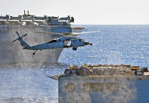 An MH-60S Seahawk helicopter assigned to Helicopter Sea Combat squadron 25 positions itself to pick up cargo from the the fleet replenishment oiler Tippecanoe during a vertical replenishment on Sunday onboard the amphibious dock landing ship Ashland. | Military Times >>