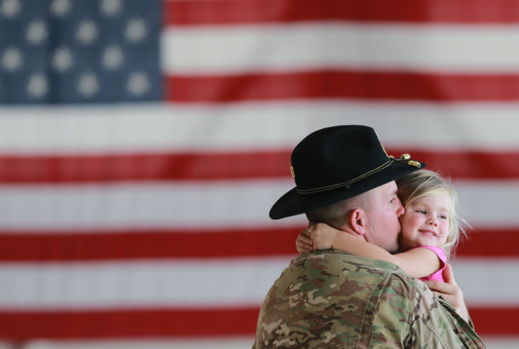 Army 1st Lt. Derek Phillips kisses his daughter, Leah Phillips, 2, as she gives him a hug at the conclusion of a casing of the squadron colors ceremony at Fort Bliss' Biggs Army Airfield in El Paso, Texas. | Military Affairs >>