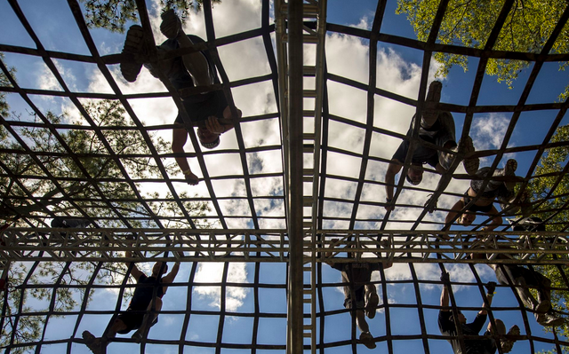 Participants climb over a rope obstacle during a Spartan Sprint race at Fort Bragg, N.C. Fort Bragg hosted the race, which drew more than 6,800 participants, at Smith Lake Recreation Area. The race was more than five miles and had more than 25 obstacles along the course.  | Military Times >>