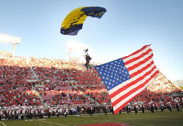 Jim Woods, a retired Navy SEAL attached to the Navy parachute team, the Leap Frogs, presents the American flag as he comes in for a landing during a demonstration before a football game between the University of Utah and Utah State University at Rice-Eccles Stadium.  | Military Times >>