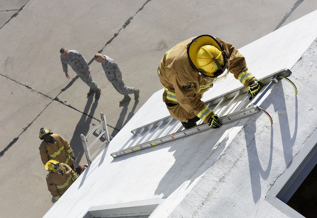 An Air National Guard firefighter assigned to the 180th Fighter Wing ascends a ladder during a regularly scheduled drill training exercise in Swanton, Ohio, at a specialized training facility owned by the Toledo Fire Department. | Military Times ><figcaption id=