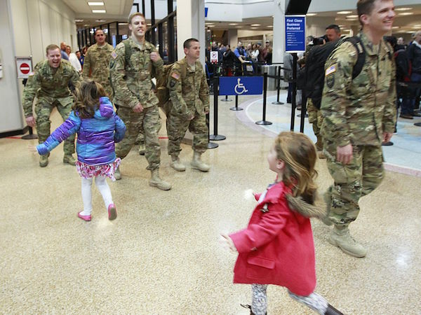Children run to members of the Utah National Guard as they walk past security and return home for the holidays at the Salt Lake City International Airport in Salt Lake City, Utah. They are part of the Utah National Guard's 141st Military Intelligence Battalion, returning from Afghanistan where they have been deployed since February. | Military Times >>