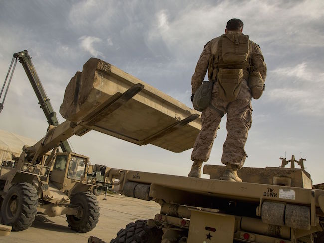 Marine Corps Sgt. Don Killian, motor transport operator with Special Purpose Marine Air-Ground Task Force — Crisis Response — Central Command, monitors Alaskan barriers as they are placed on a flatbed at Al Taqaddum Air Base, Iraq. | Military Times >>