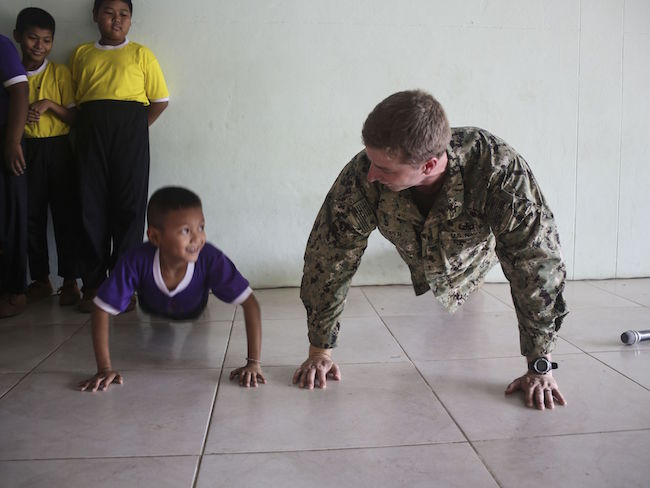 Navy Petty Officer 2nd Class Chris Keiper, an Explosive Ordnance Disposal Technician with Mobile Unit 3 deployed to Mobile Unit 5, does pushups with students at the Kao Chi Chan School during exercise Cobra Gold in Sattahip, Thailand. Lance Cpl. Jeremy Laboy/Marine Corps | Military Times >>