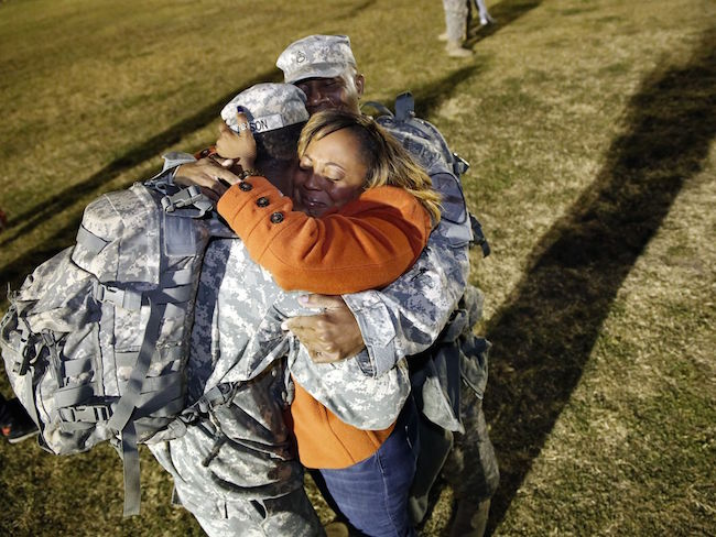Tarnisha Gibson, center, hugs her son, Spc. Bradley Gibson, left, and husband, Staff Sgt. Corwyn Gibson, on Feb. 11 during a homecoming celebration at Fort Hood's Cooper Field in Fort Hood, Texas.  Eric J. Shelton/The Killeen Daily Herald via AP | Military Times ><figcaption id=