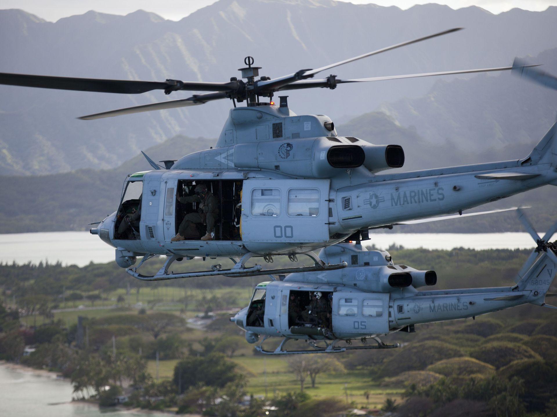 Two Marine Corps UH-1Y Huey Helicopters fly from Marine Corps Base Hawaii to the North Shore of Oahu, Hawaii, during a personnel transportation exercise.  Lance Cpl. Julian Temblador/Marine Corps | Military Times ><figcaption id=