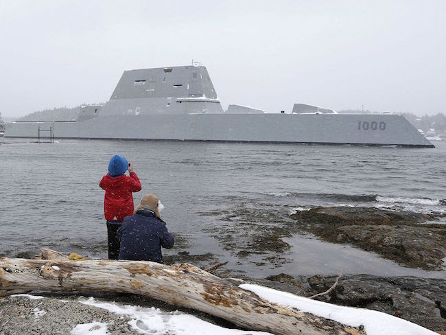 Dave Cleaveland and his son, Cody, photograph the destoryer as it passes Fort Popham at the mouth of the Kennebec River in Phippsburg, Maine, in late March as it heads to sea for final builder trials. The ship is so stealthy that the Navy resorted to putting reflective material on its halyard to make it visible to mariners during the trials. Robert F. Bukaty/AP